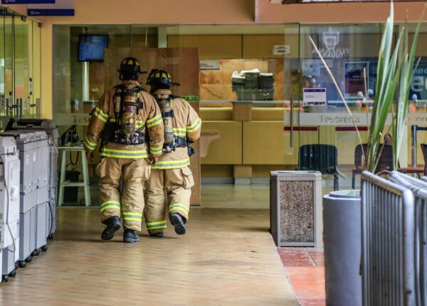 fire men walking through commercial building after life safety solutions enacted